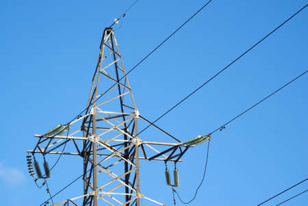 Top of high-voltage power line grey metal tower photo
