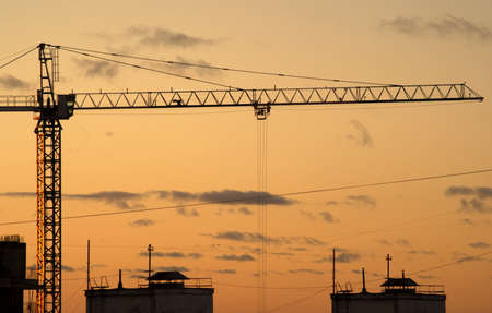 Hoisting tower crane and the contours of house under construction sunset view photo