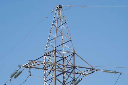 isolators: Top section of high-voltage power line metal tower isolated on blue