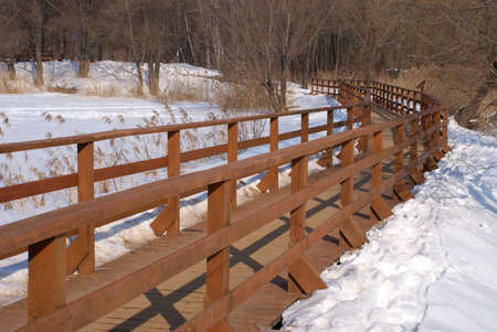 Long wooden pedestrian bridge with fence winter view photo