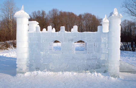 Toy ice castle in winter forest photo