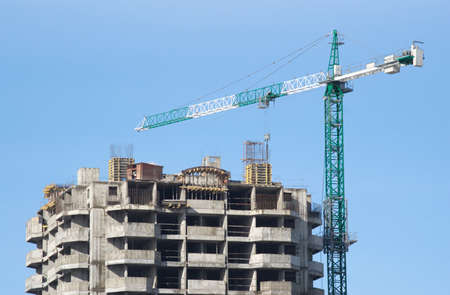 Big hoisting tower crane and top of construction building isolated on blue Stock Photo - 12910493