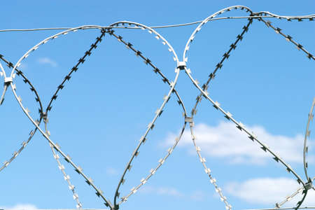 Barbed twisted wire on sky with white clouds photo