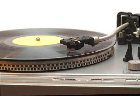 Turntable with vinyl record with yellow label isolated on white closeup photo
