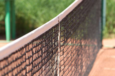 Tennis net on ground court closeup photo
