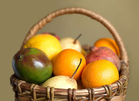collected: Lot of fruits collected in brown wicker basket isolated closeup Stock Photo