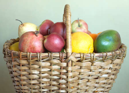 Brown wicker basket with lot of assorted fruits closeup photo