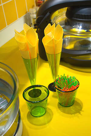 Many napkins in glasses and kitchen equipment on yellow desk closeup photo