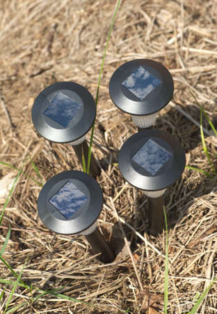Four solar power lantern with sky and clouds reflected in solar elements in dry grass close up photo