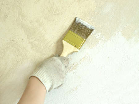 Woman s hand in white fabric protective glove holds brush and paint wall repair vertical photo photo