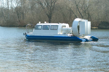hovercraft: Hovercraft slow floats on a river in spring day