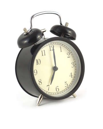 Alarm clock in black case shows 7 hours  Side view isolated on white close up photo