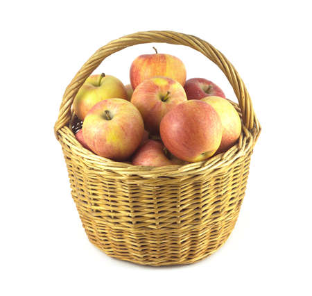 Many red and yellow ripe apples in brown wicker basket isolated on white vertical view photo