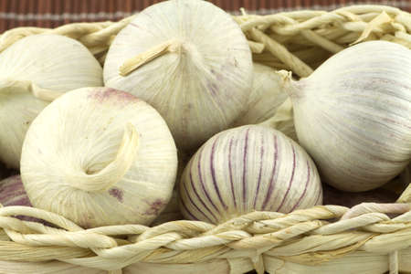 Ripe fragrant garlic in wicker basket on straw mat macro photo