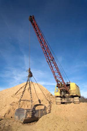 crane bucket: Big excavator with heavy bucket on sand mountain close up