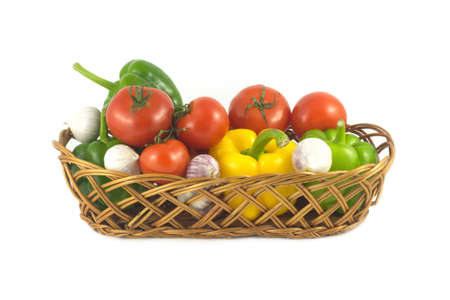 Lot of assorted ripe vegetables in brown wicker basket isolated on white close up photo