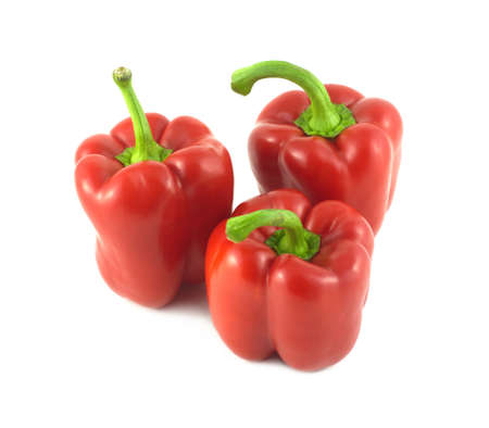 Three whole red ripe bell peppers isolated on white close up photo