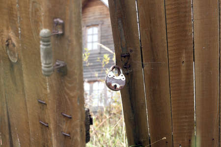 Hanging metal lock on a wooden fence and an abandoned farmhouse behind it photo