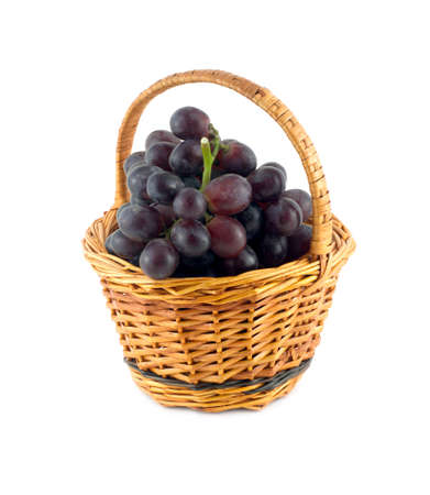 Red grape on branch in brown round wicker basket isolated on white close up photo