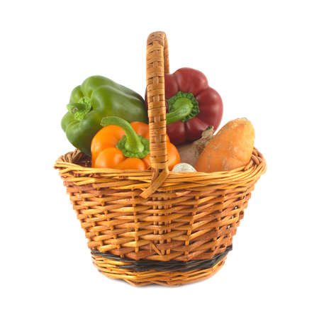 Many different vegetables in brown wicker basket isolated on white closeup photo