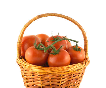 Many red ripe tomatoes on branch inside brown wicker basket isolated on white closeup photo