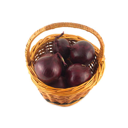 Purple onion turnip in brown round wicker basket isolated on white closeup photo