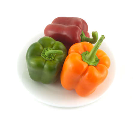 Three fresh sweet peppers on plate isolated over white background close up photo
