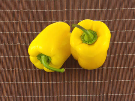 Two yellow bell peppers on brown wicker straw mat close up photo