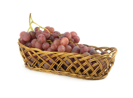 Red grape on branch in brown wicker basket isolated on white side view  Stock Photo