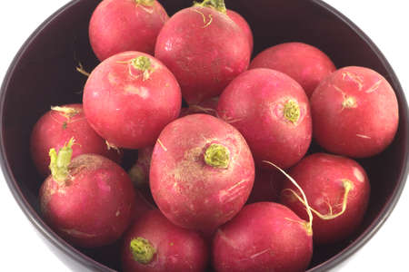 Many red radishes in purple bowl closeup isolated on white photo