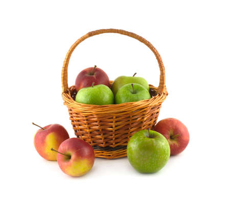 Many ripe color apples in brown wicker basket and near it isolated on white closeup photo