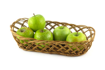 Five ripe green apples in long brown wicker basket isolated on white closeup photo