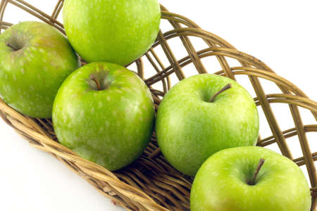 Ripe green apples in long brown wicker basket isolated on white closeup photo