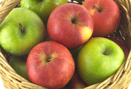 Ripe green and red apples in brown wicker basket isolated on white closeup photo