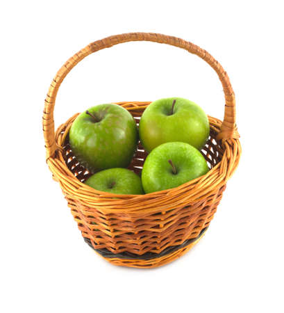 Ripe green apples in brown wicker basket isolated on white closeup photo