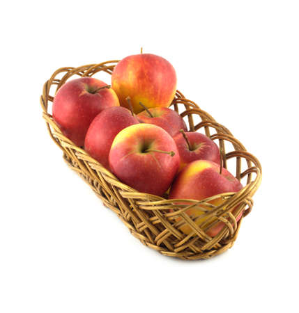 Ripe red apples in long brown wicker basket isolated on white diagonal view closeup photo