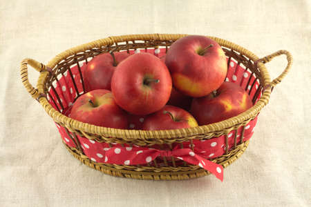 Ripe red apples in long brown wicker basket on beige fabric front view closeup photo