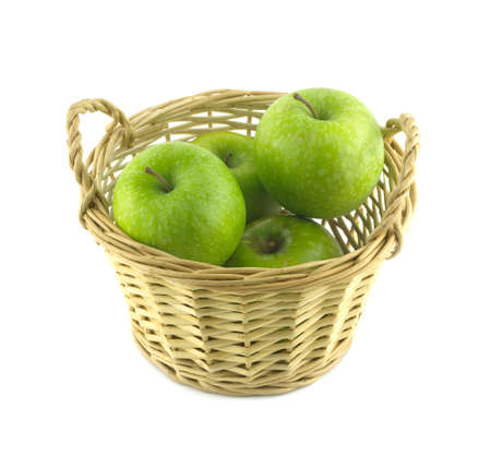 Ripe green apples in light brown wicker basket isolated on white closeup photo