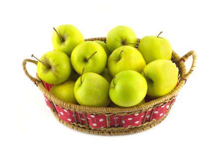 Ripe yellow apples in long brown wicker basket isolated on white closeup photo