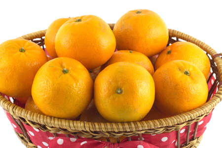 Many orange tangerines in long brown wicker basket isolated on white closeup photo