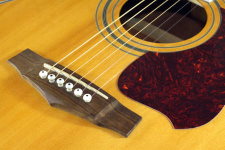showbusiness: Classic acoustic guitar natural color top fragment with six strings closeup