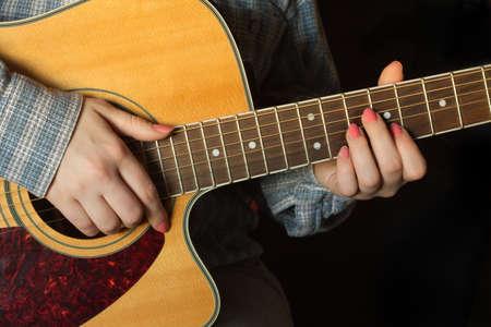 chemise carreaux: Jeune fille en chemise � carreaux avec manucure rose jouant une guitare acoustique sur l'obscurit�