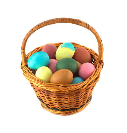 Colorful Easter eggs inside straw wicker brown basket isolate on white closeup photo