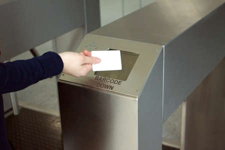 Woman s hand puts white plastic card to reader access control space closeup photo