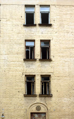 Abandoned uninhabited house with broken windows before renovation front view vertical closeup photo