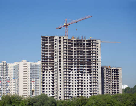 Long hoisting tower crane in construction new apartment building process over cloudless sky photo