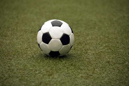 pasto sintetico: Bola blanco y negro cl�sico para jugar al f�tbol en c�sped sint�tico de cerca Foto de archivo