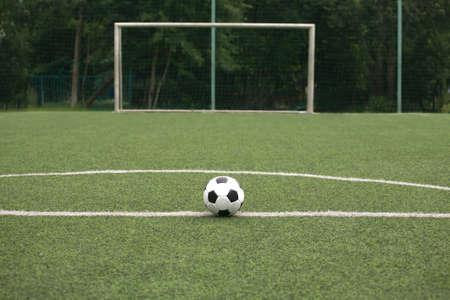 prato sintetico: Palla bianca e nera Classic per giocare a calcio in erba sintetica parco giochi contro il cancello sul campo sportivo di close-up