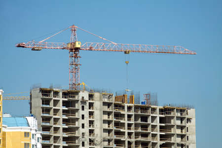 single dwellings: Big hoisting tower crane over top of construction building under cloudless sky Stock Photo