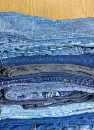 sandy brown: Many colored jeans on on sandy brown background vertical view close-up